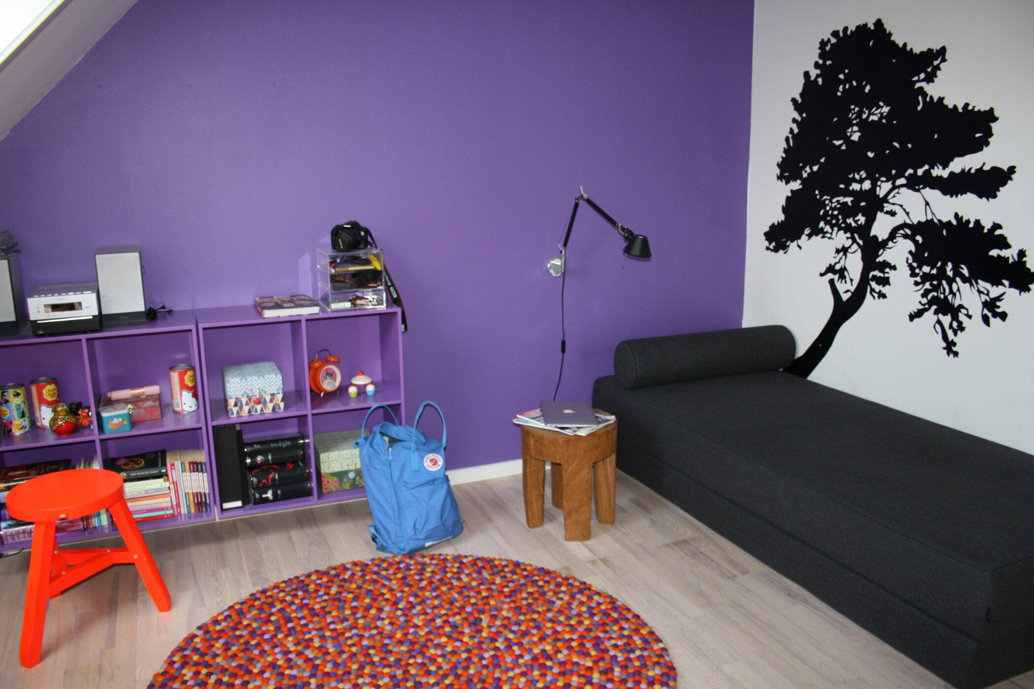 Rummet er blevet levende ved at male væggen lilla. Endvidere er bogkasserne male i samme farve, for at skabe ro i helhedsoplevelsen af rummet