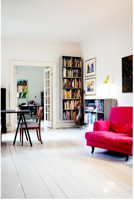 Ny boligindretning: De slidte trægulve er blevet malet i en lys grå farve, som indeholder lidt gult, for at få varme i rummet. Farven er nøje afstemt i forhold til øvrigt inventar. En pink lænestol er anskaffet og reoler og billeder er ophængt.