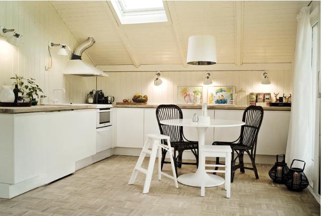 Køkkenet er redesignet og har udover væggen ved vask og komfur, fået yderligere en skabsvæg under skråvæggen. Modulerne her er kun 40 cm. i dybden og fungerer som aflastning og gør rummet mere helstøbt. Al træværk er malet i en knækket hvid og bidrager med mere lys i rummet.